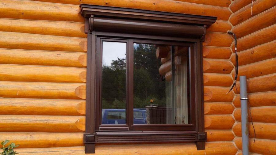 Деревянные окна в коттедже из бревна с наличниками окно