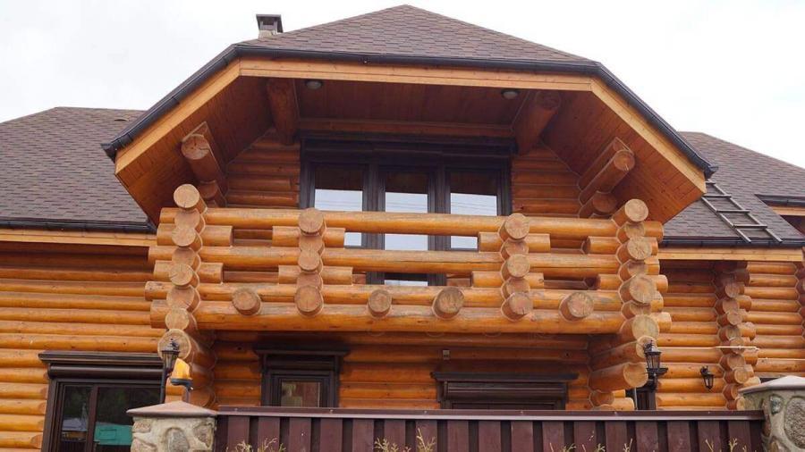 Деревянные окна в коттедже из бревна с наличниками вид спереди